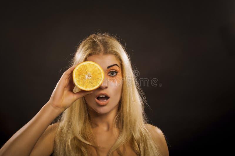 女孩用桔子 库存照片