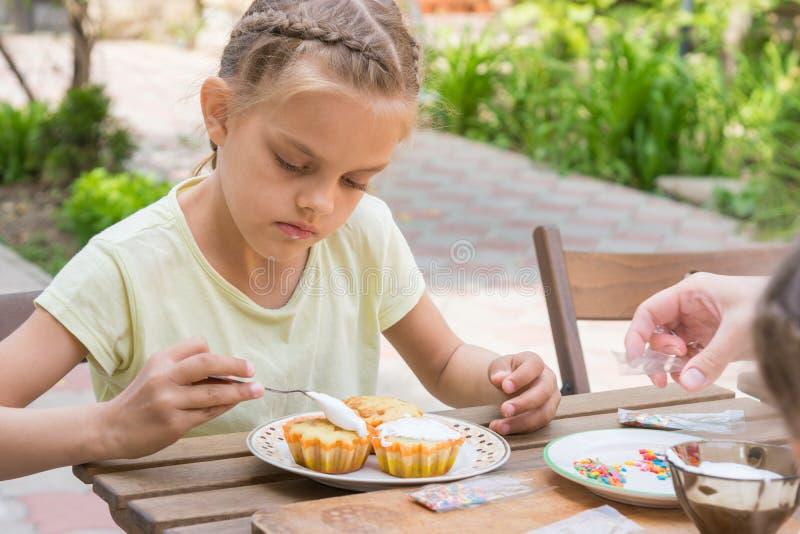 女孩用糖果店釉复活节杯形蛋糕小心地涂 免版税库存照片