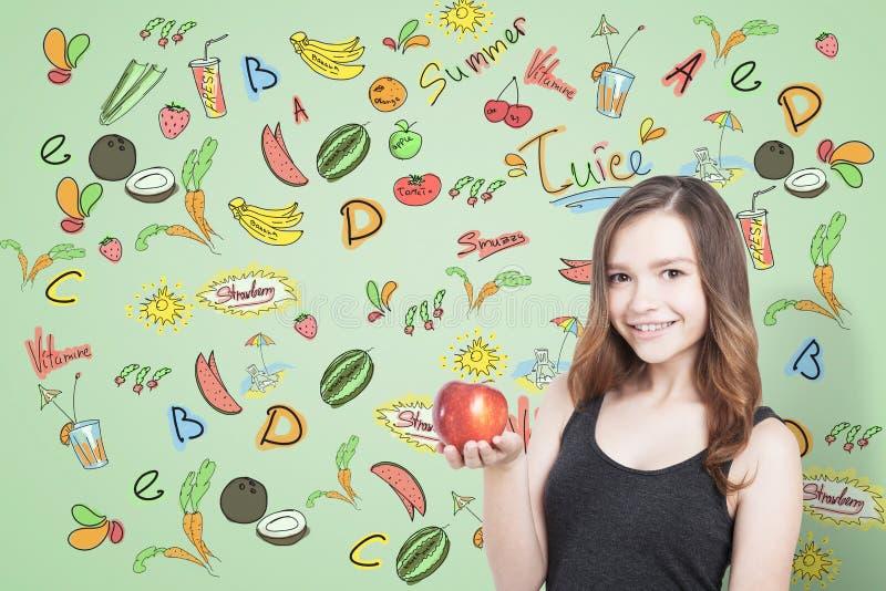 女孩用苹果和果子,绿色 库存照片