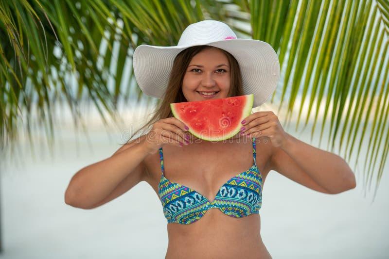 女孩用西瓜在棕榈树下 免版税库存图片