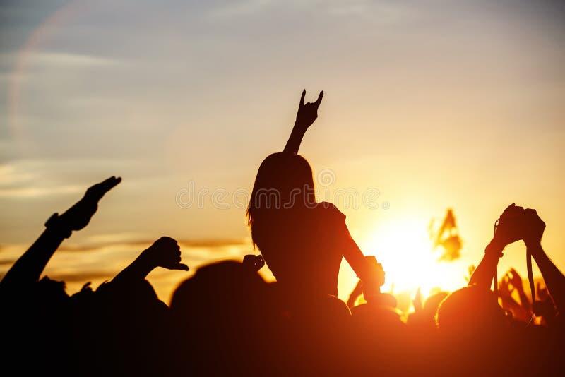 女孩用跳舞的手,唱歌和听音乐在夏天音乐节的音乐会展示期间 免版税库存照片