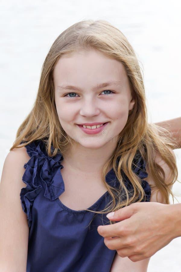 女孩用长的金发和母亲手 免版税库存照片