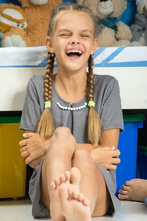 女孩由床快乐地笑坐 库存图片