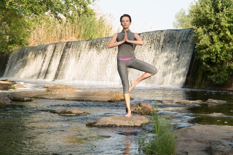 女孩由水占去瑜伽 免版税库存照片