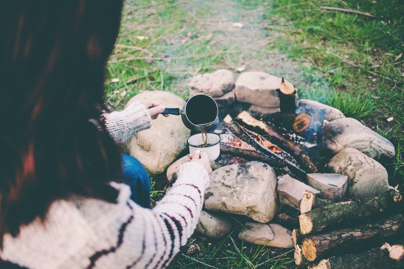 女孩由火喝咖啡 免版税图库摄影