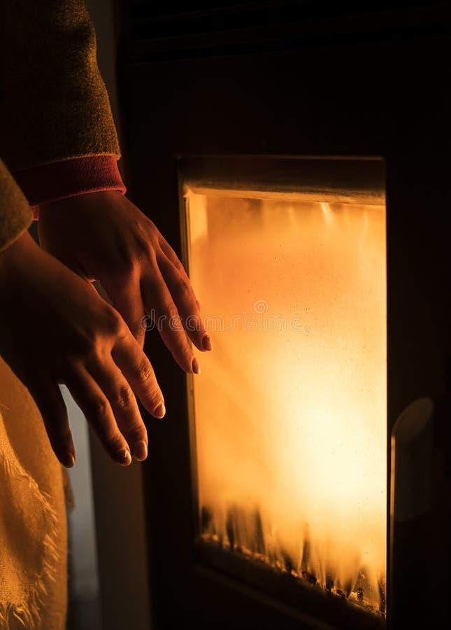 女孩由熔炉加热她的手 免版税图库摄影