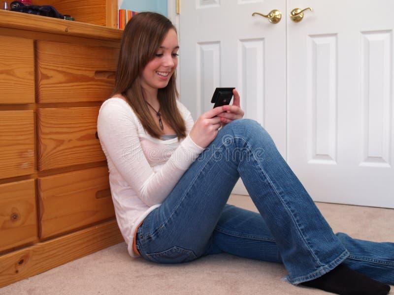 女孩电话少年texting 免版税库存照片