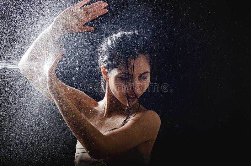 女孩画象和飞溅水在她的面孔 在黑背景的美好的女性模型 库存图片