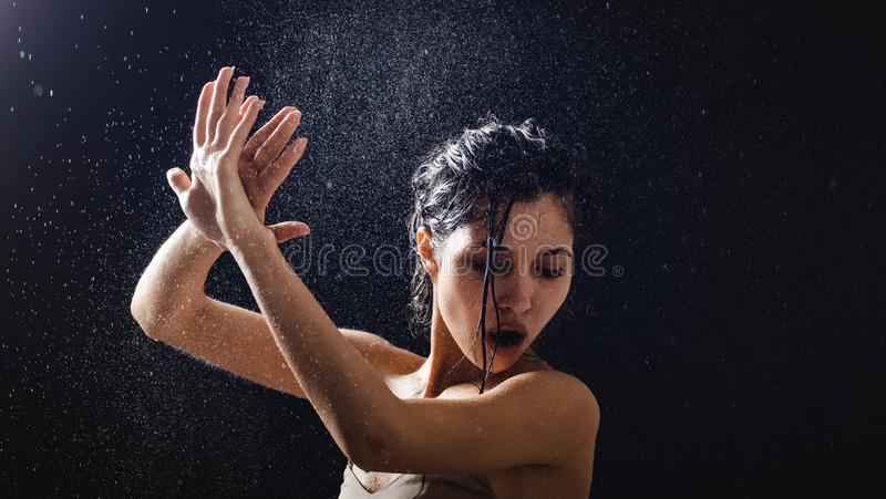 女孩画象和飞溅水在她的面孔 在黑背景的美好的女性模型 免版税库存照片