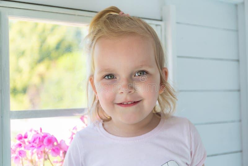女孩画象在她的庭院房子里面的 图库摄影