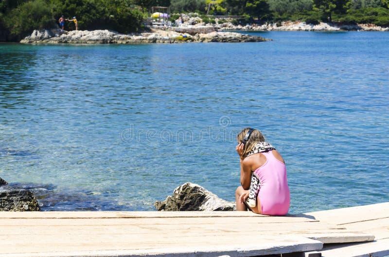 女孩画象比基尼泳装的有坐码头和听到音乐的耳机的 免版税库存照片