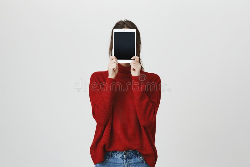 女孩画象盖她的面孔的时髦红色毛线衣的用站立在白色墙壁附近的片剂 技术和小配件 免版税库存照片