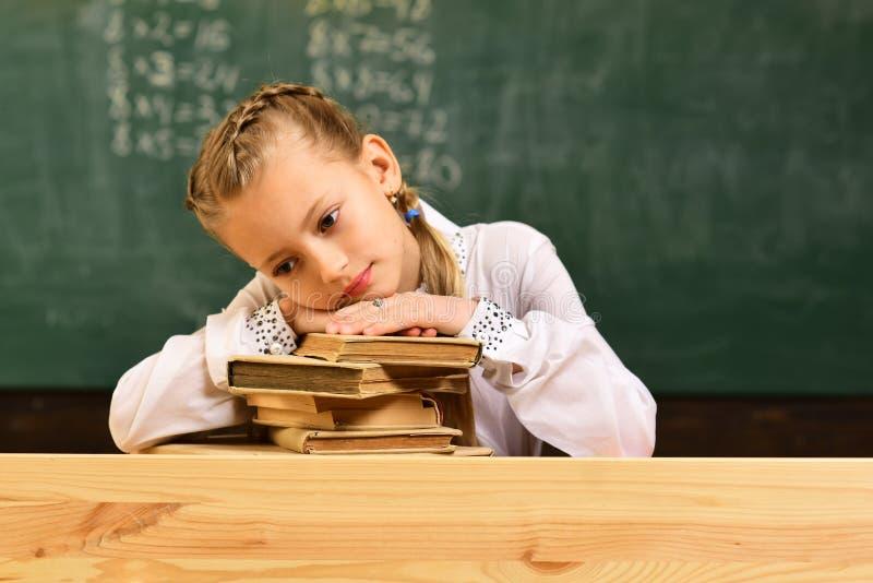 女孩疲倦 学校教训的疲乏的女孩 疲乏的女孩准备对检查 有书的小疲乏的女孩在桌上 感觉 免版税库存图片