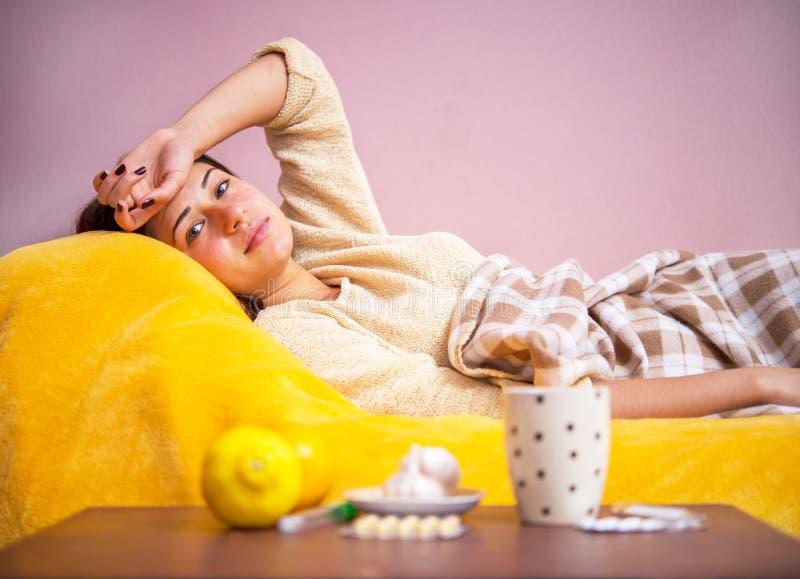 女孩病残在盖子下的床上 图库摄影