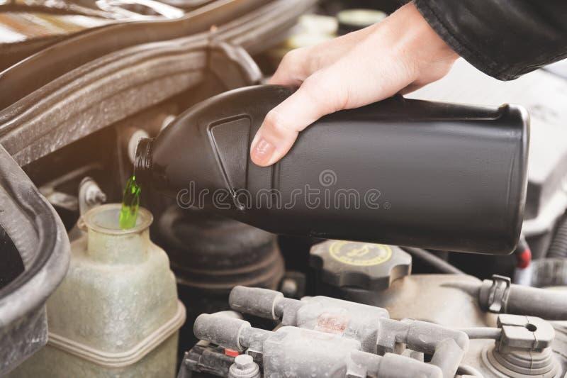 女孩的关闭检查蓄冷剂的水平在她的汽车引擎的  库存照片