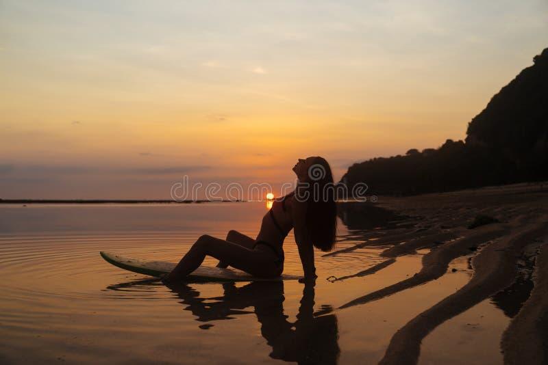 女孩的剪影和反射坐冲浪板在美好的日落背景的海洋海滩  免版税库存照片