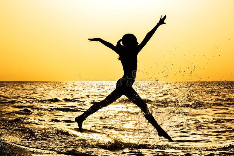 女孩的剪影,跑沿海滨在日落 免版税图库摄影