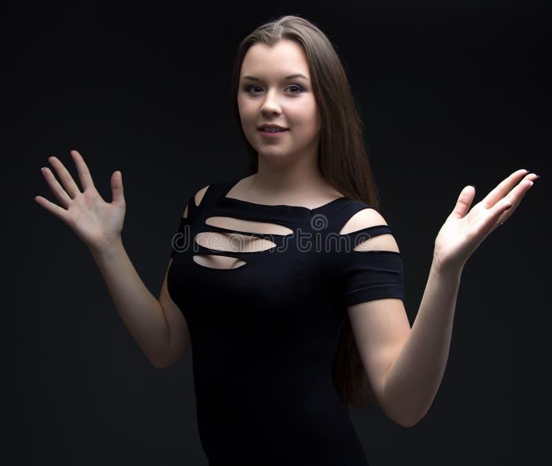 女孩的图象黑礼服的用开放手 图库摄影