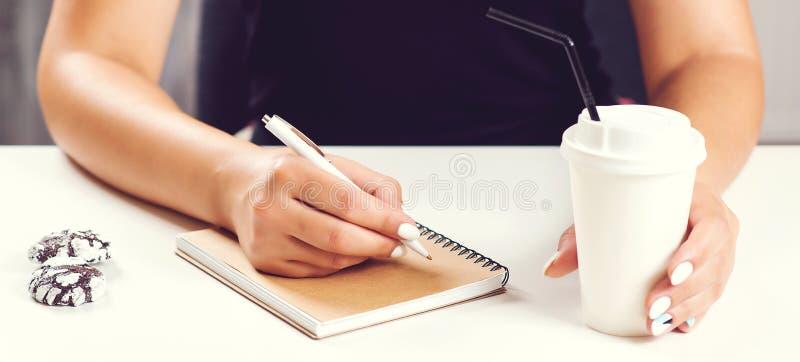 女孩的在与咖啡杯的白色表面安置的笔记薄的手文字 嘲笑 采取妇女的附注 背景中断咖啡新月形面包杯子甜点 创造性的工作 库存照片
