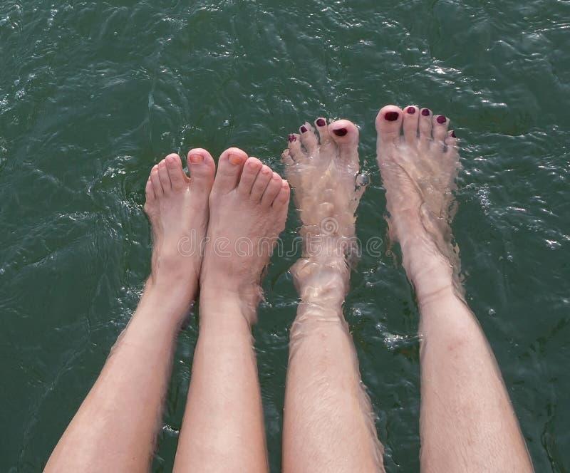 女孩的在水池制造的秀丽腿飞溅浅深度  免版税库存图片