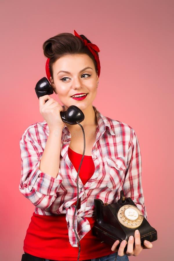 女孩的愉快的别针谈话在减速火箭的电话 库存照片