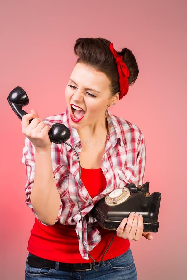 女孩的愉快的别针谈话在减速火箭的电话 免版税图库摄影