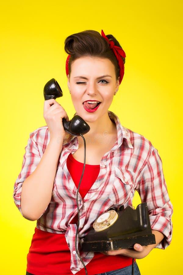 女孩的愉快的别针谈话在减速火箭的电话 免版税库存图片