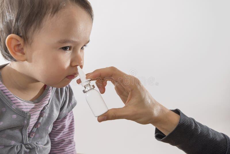 女孩的父母的手应用鼻孔喷射于她 库存图片