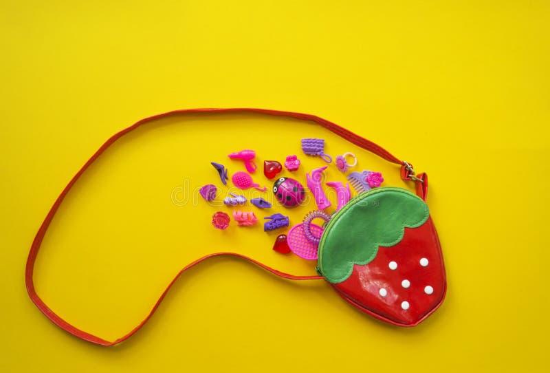 女孩的玩具 平的位置桃红色在黄色背景戏弄 免版税库存照片