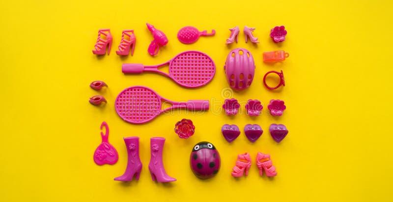女孩的玩具 平的位置桃红色在黄色背景戏弄 免版税库存图片