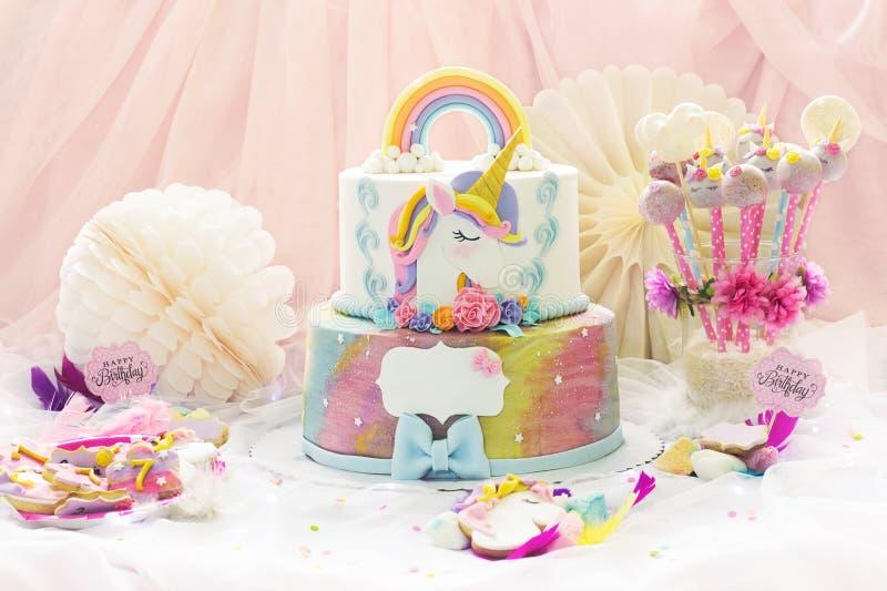 女孩的生日宴会;与独角兽蛋糕、蛋糕流行音乐、糖屑曲奇饼和生日装饰的点心桌 免版税库存图片
