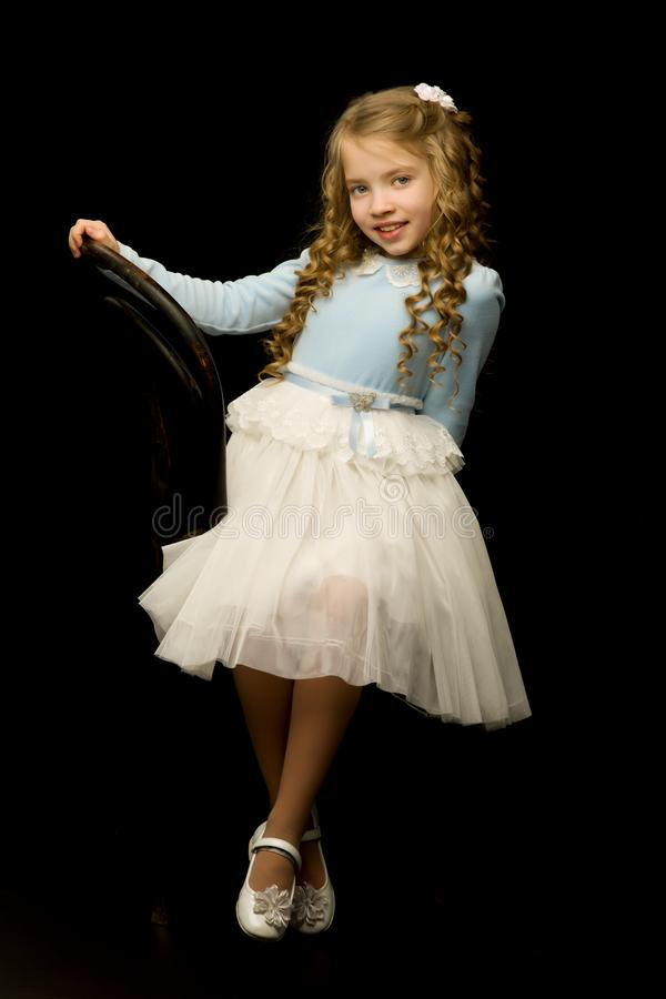 女孩的画象坐一把老维也纳椅子,blac 免版税库存照片