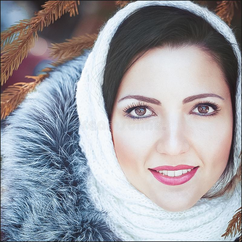女孩的画象,冬天,特写镜头 年轻美丽的愉快的微笑的女孩佩带的白色被编织的童帽画象的室外关闭  库存照片