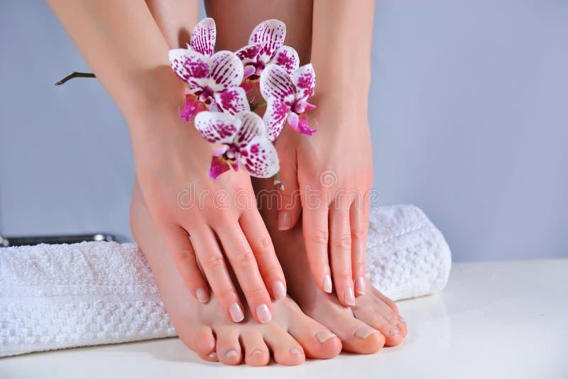 女孩的脚和手,用毛巾上的天然光亮色美甲和修脚 库存图片
