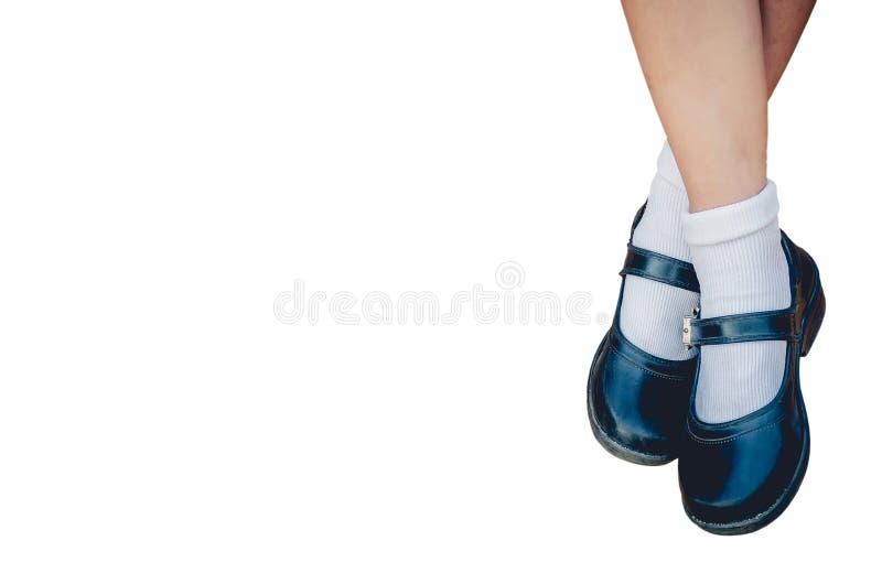 女孩的脚在与裁减路线的白色背景穿一名有隔绝的黑学生鞋子 免版税库存图片