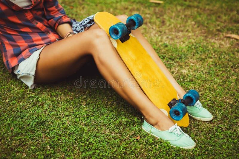 女孩的腿有滑板的 免版税库存图片