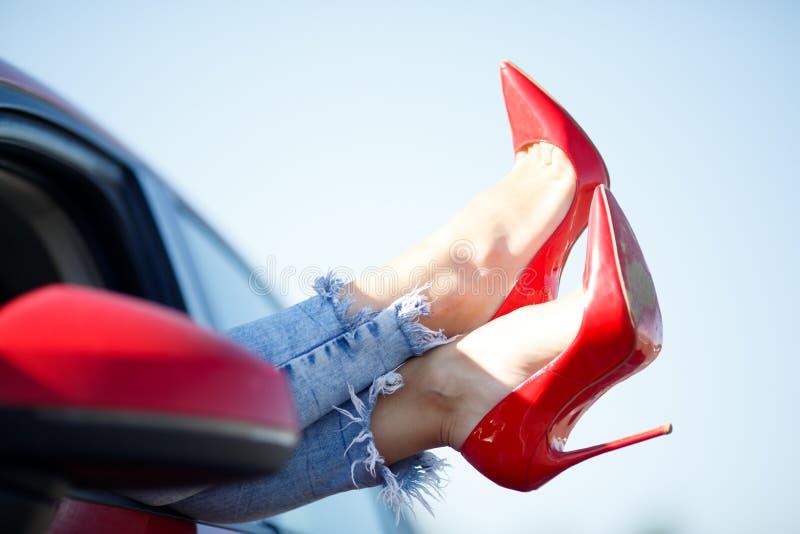 女孩的腿的图象在黏附在红色车窗外面的红色鞋子的 库存照片