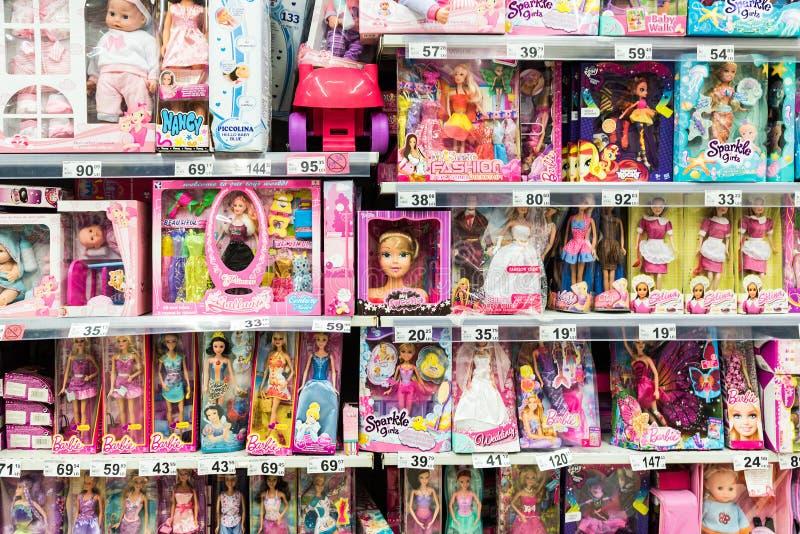 女孩的芭比娃娃玩具和在超级市场立场的其他婴孩玩具 库存照片