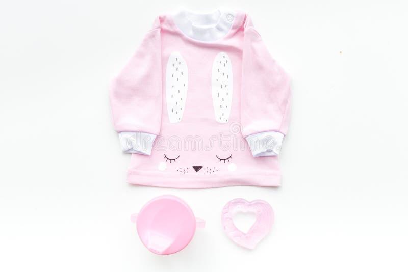 女孩的逗人喜爱的桃红色婴孩衣裳 衬衣,玩具,在白色背景顶视图拷贝空间的瓶 库存照片