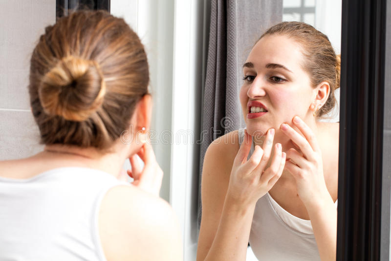 女孩的镜象反射有紧压她的丘疹的粉刺的 免版税库存图片