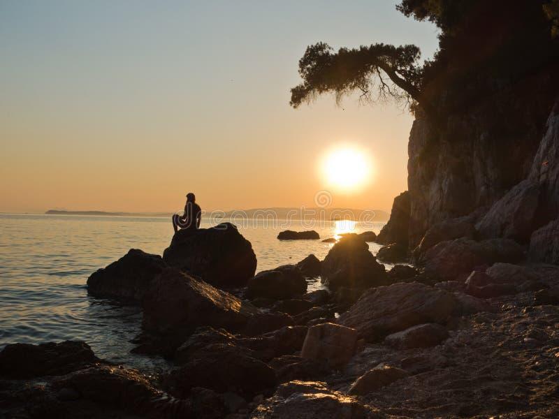 女孩的Sihouette坐岩石在日落, Kastani妈妈Mia海滩,斯科派洛斯岛海岛  免版税库存照片