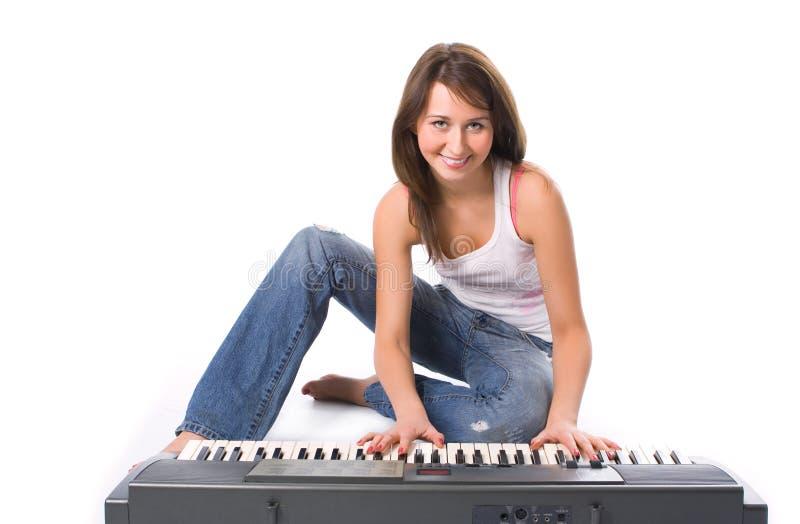 女孩相当钢琴作用 免版税库存照片
