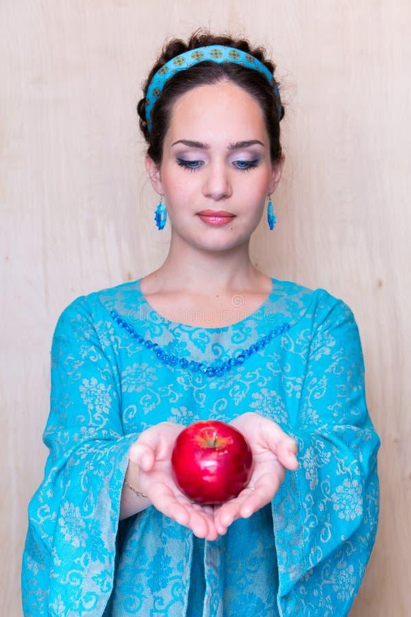 女孩看举行它在她前面的红色苹果计算机 免版税库存照片