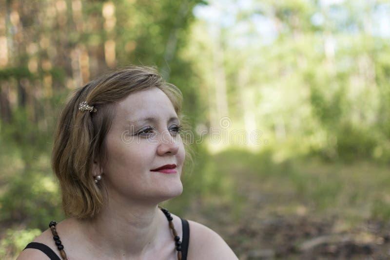 女孩看对天空 看斜向一边在一个公园的妇女在夏天 免版税库存照片