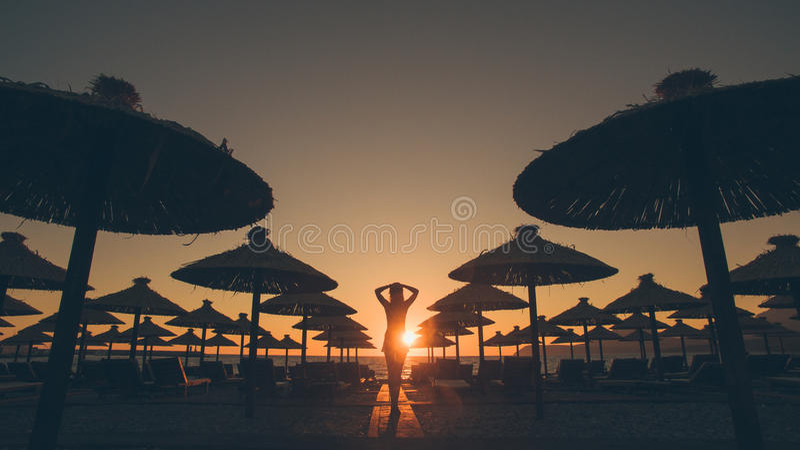 女孩看看在海滩剪影的日落 库存图片