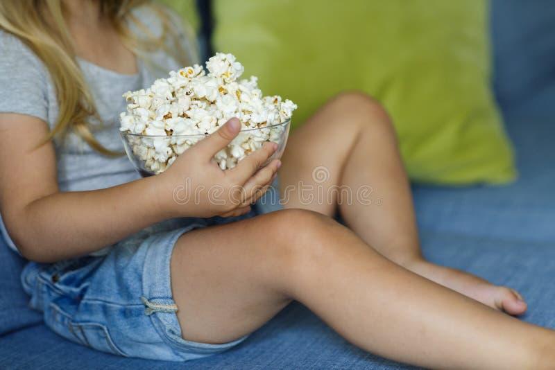 女孩看着电视 拿着一个碗用玉米花的愉快的逗人喜爱的女孩 免版税库存图片