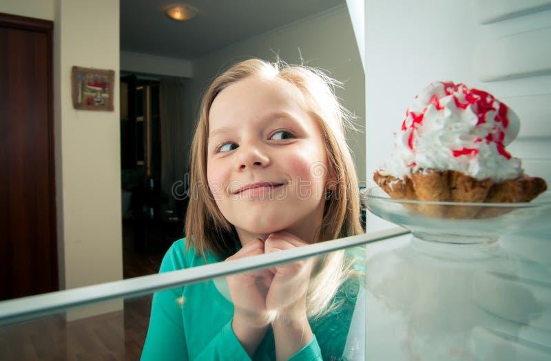 女孩看见甜蛋糕 免版税库存图片