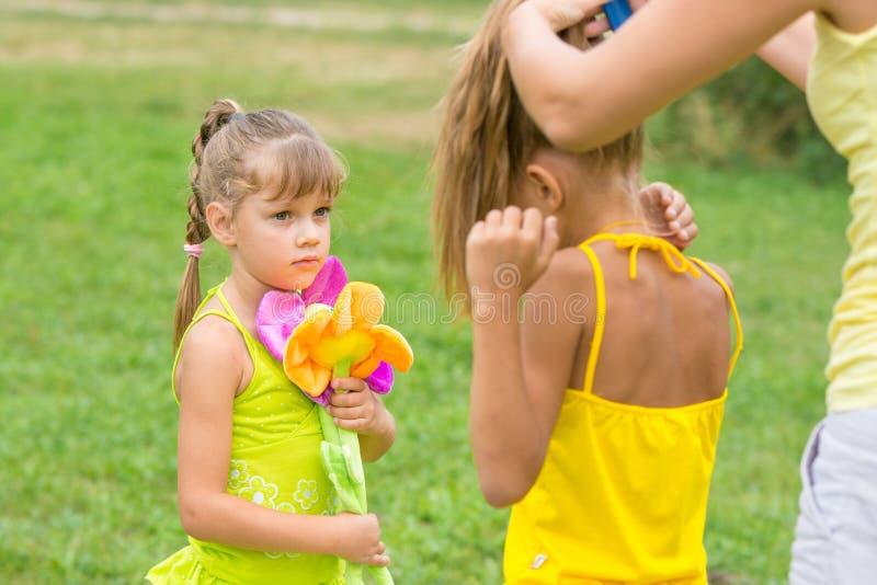女孩看起来我的母亲把她的姐妹编成辫子 图库摄影