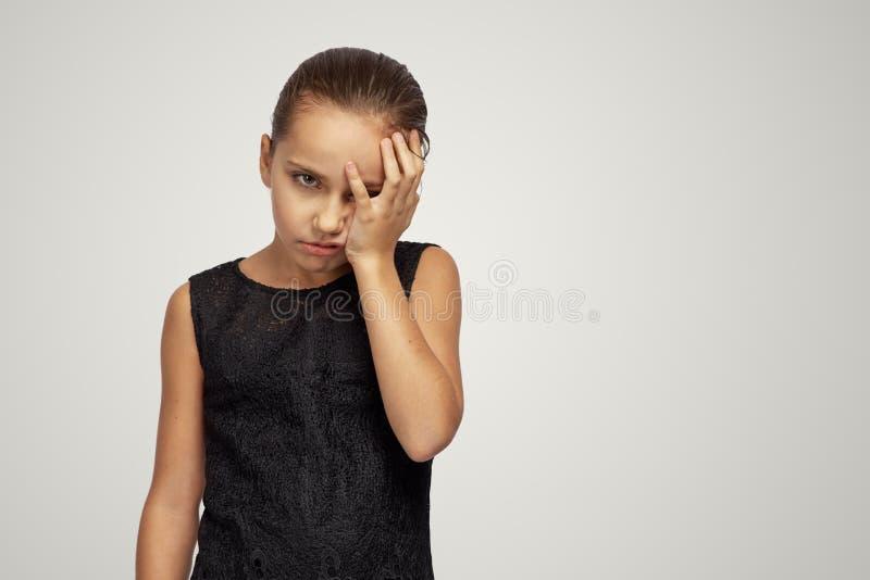 女孩看起来被弄翻在照相机和关闭她的面孔用她的在羞辱的手 失败,损失,失望的概念 免版税图库摄影