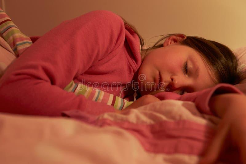 女孩睡着在床上在晚上 库存图片